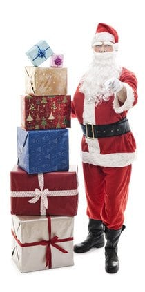 Santa Claus standing next to a stack of gifts, pointing