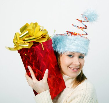 Young woman holding a present up to her ear